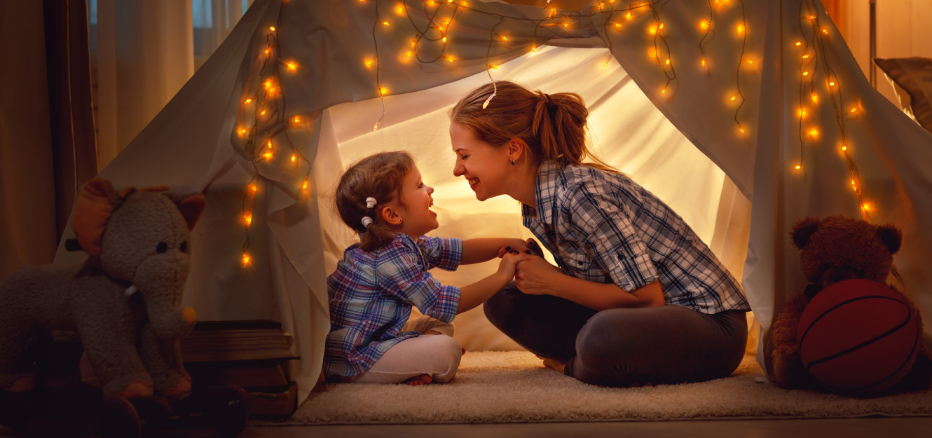a mother and daughter playing in a tent
