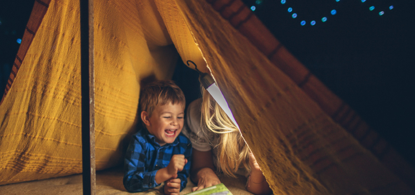 a little boy playing in a tent